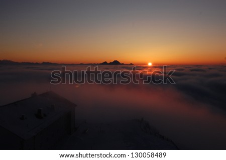 Winter landscape with sunset above the clouds, taken from the mountain Rigi, Switzerland. Mountain Pilatus is in the background. - stock photo