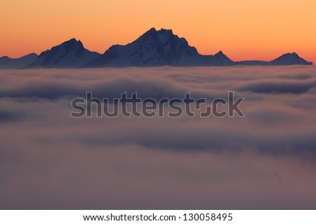 Winter landscape with sunset above the clouds, taken from the mountain Rigi, Switzerland. Mountain Pilatus is in the background - stock photo