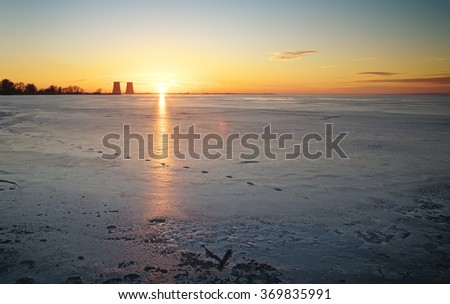 Winter landscape with sunset, frozen lake and power plant. - stock photo