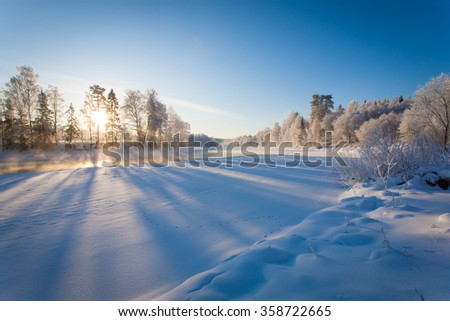 Winter landscape with the river at dawn - stock photo