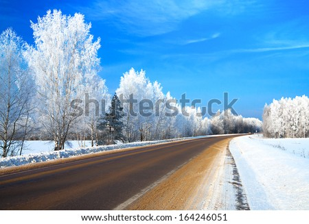 winter landscape with the road the forest and the blue sky - stock photo