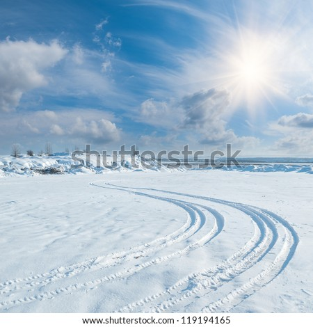 Winter landscape with tire trace on snow leaving to the horizon, sun and clouds in sky - stock photo