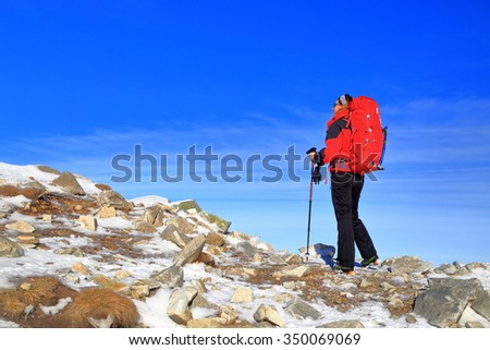 Winter landscape with woman mountaineer climbing snow covered ridge, Retezat mountains, Romania - stock photo