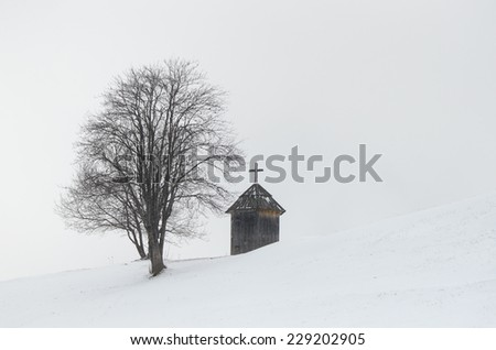 Winter landscape. Wooden chapel and a tree on a hill. The village is in the mountains. Carpathians, Ukraine, Europe  - stock photo