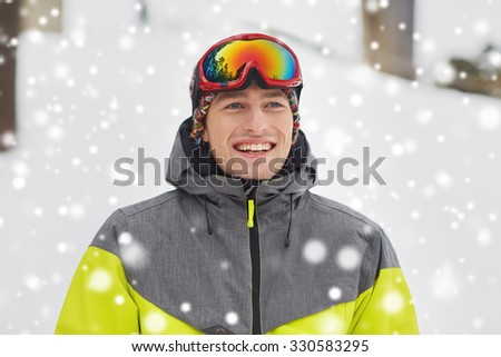 winter, leisure, sport and people concept - happy young man in ski goggles outdoors - stock photo