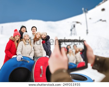winter, leisure, sport, friendship and people concept - group of smiling friends with snow tubes taking picture by tablet pc computer over mountain background - stock photo