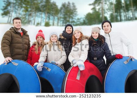 winter, leisure, sport, friendship and people concept - group of smiling friends with snow tubes outdoors - stock photo