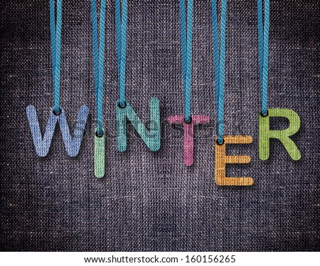 Winter letters hanging strings with blue sackcloth background. - stock photo