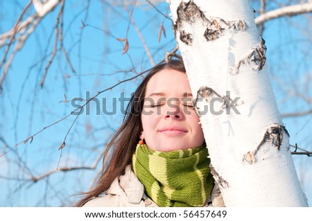 Winter lifestyle. Beautiful girl with green scarf and gloves over birch tree and blue sky
