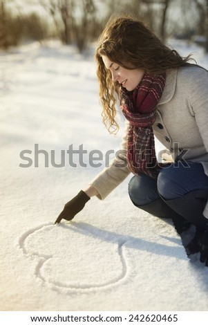Winter love, young girl drawing a heart shape in a snow - stock photo