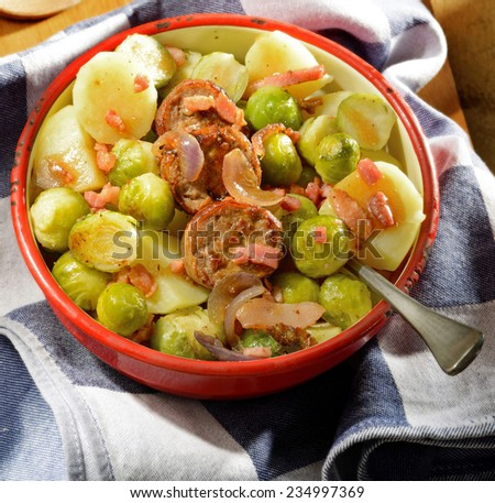 Winter meal. Seasonal fare with potatoes, Brussels sprouts and sausage slices garnished with onion and bacon in rustic enamel serving dish.  - stock photo