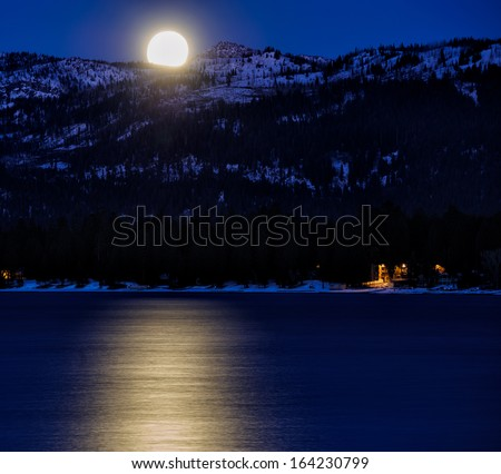 Winter Moon over Frozen Lake - stock photo