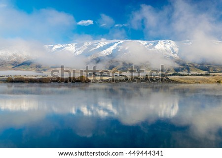 Winter morning view of Pisa range (part of the southern alps reflected in lake Dunstan, Cromwell, New Zealand - stock photo