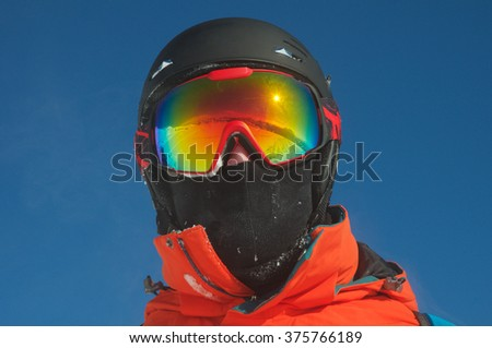 Winter mountain landscape and ski slope reflected in a ski mask. Selective focus. - stock photo