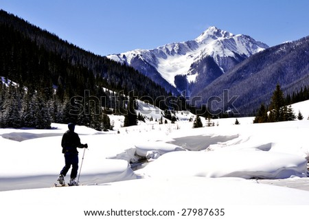 winter mountain landscape with adult male skiing toward distant peak - stock photo