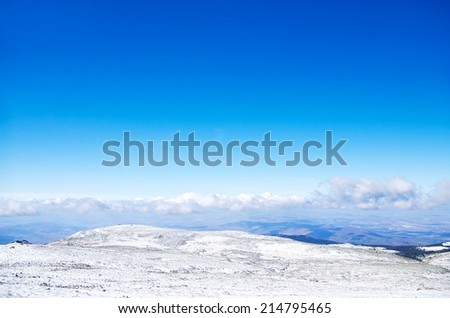 Winter mountain landscape with low flying clouds