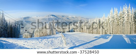 Winter mountain landscape with ski lift and skiing slope. Bukovel ski resort, Ukraine. Three shots stitch image.