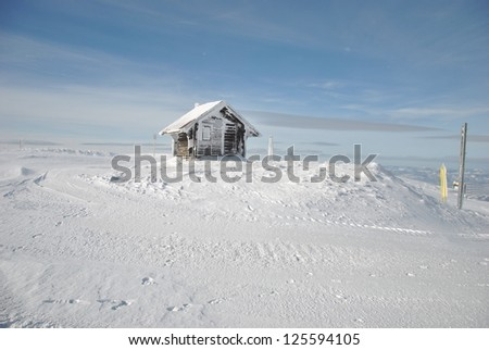 Winter mountain landscape with small shelter house and snowy pillars - stock photo