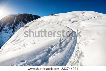 Winter mountain scenery at blue sky with sun