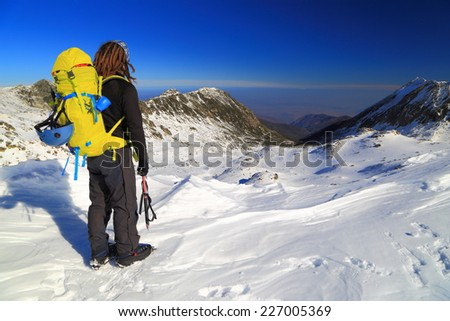 Winter mountaineer admiring the view of snow covered mountains - stock photo