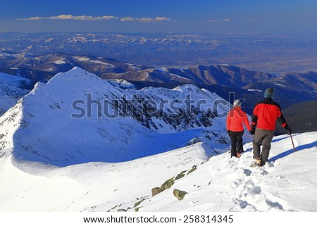 Winter mountaineers descending along snowy ridge above the mountains - stock photo
