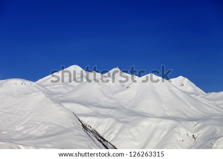 Winter mountains and blue sky. Caucasus Mountains, Georgia, region Gudauri. - stock photo