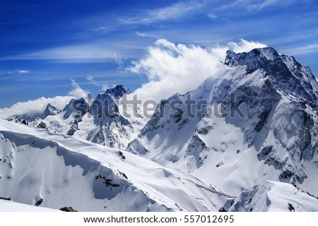 Winter mountains with snow cornice and blue sky with clouds in nice sun day. Caucasus Mountains, region Dombay. Mount Dombai-Ulgen. View from the top of Musa Achitara.