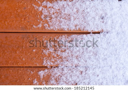 Winter nature background pattern abstract contrast of fresh snow melting on wet wooden deck plank surface - stock photo