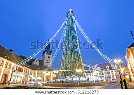 Winter night cityscape with Christmas tree in the historic center of Cisnadie (Sibiu county), Transylvania, Romania