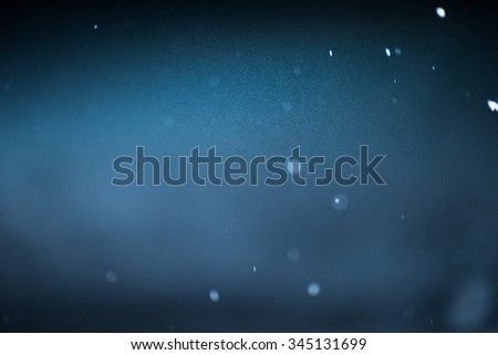 winter night scene, falling snow background snowflakes in blur over dark background - stock photo