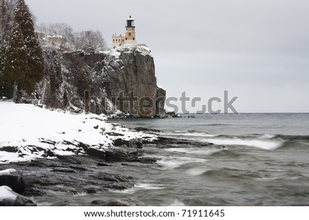 Winter on Lake Superior with a lighthouse on a cliff. - stock photo