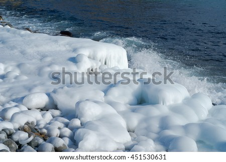 Winter on sea: stones with ice, seawater and surf. - stock photo