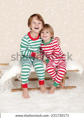 Winter or Christmas Holidays: laughing, smiling, happy kids in red and green striped pj pajamas on wood sled in fake snow, snowflakes - stock photo