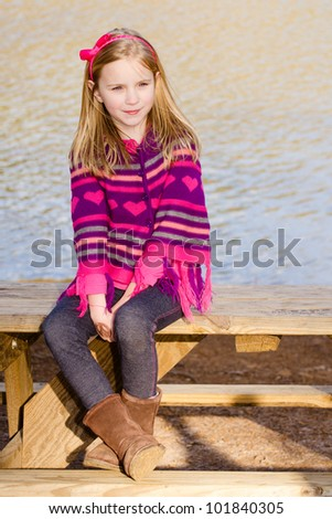 Winter or early spring portrait of pretty young girl child wearing knit poncho at park - stock photo