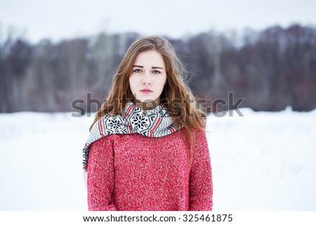 winter outdoor portrait of cure young serious girl with incredulous look with blond hair with red warm sweater and scarf on natural background in field - stock photo