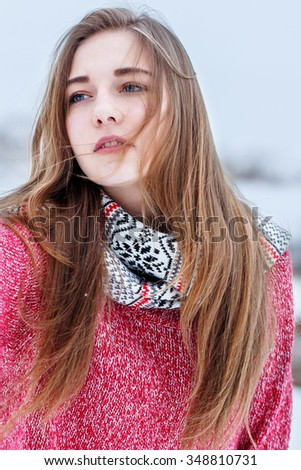 Winter outdoor portrait of cute attractive young blond girl with long hair with red sweater looking with hope in her eyes in windy cloudy weather on natural background in field - stock photo