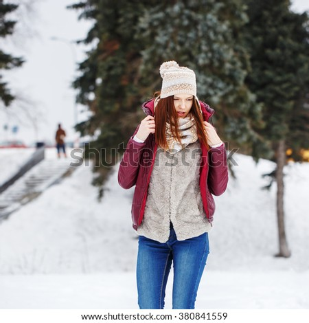 winter outdoor portrait of cute beautiful attractive young girl with heat scarf and red jacket walking in park on natural trees background - stock photo