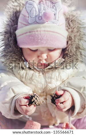 Winter outdoor portrait of little girl playing with cones - stock photo