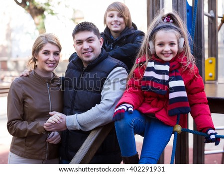 Winter outdoor portrait of ordinary family with son and daughter