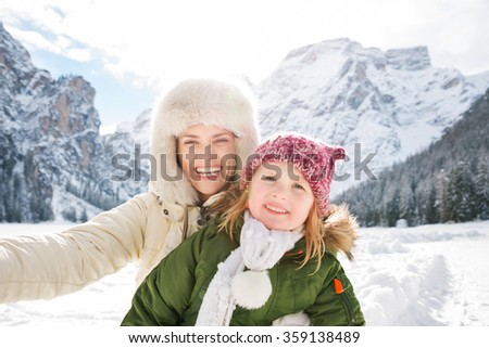 Winter outdoors can be fairytale-maker for children or even adults. Smiling mother and child taking selfie outdoors in front of snowy mountains - stock photo