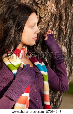Winter outfit portrait of beautiful female model posing by tree bark