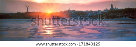 Winter panorama of sunset over the frozen Dnieper. Severe frost bound water of the river  On the background of a steep bank, we see a statue of the Motherland, and domes of Kiev Dormition Lavra - stock photo