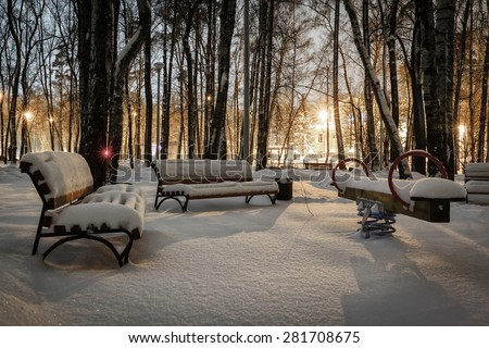 Winter park at night, benches and teeter covered with new snow with light - stock photo