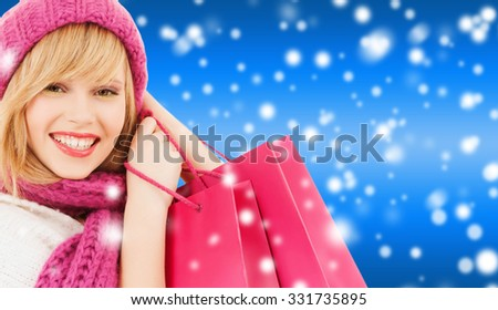 winter, people and happiness concept - woman in pink hat and scarf with many shopping bags - stock photo