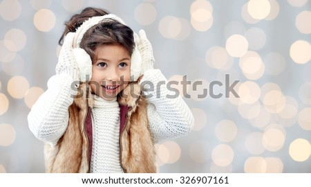 winter, people, christmas, fashion and childhood concept - happy little girl wearing earmuffs and gloves over holidays lights background - stock photo