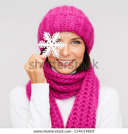 winter, people, happiness concept - woman in hat and muffler with big snowflake - stock photo