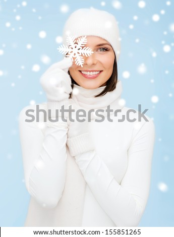 winter, people, happiness concept - woman in hat, muffler and gloves with big snowflake - stock photo