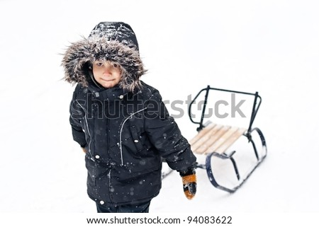 Winter photo of cute young boy in winter suit pulling snow sledges through the snow - stock photo