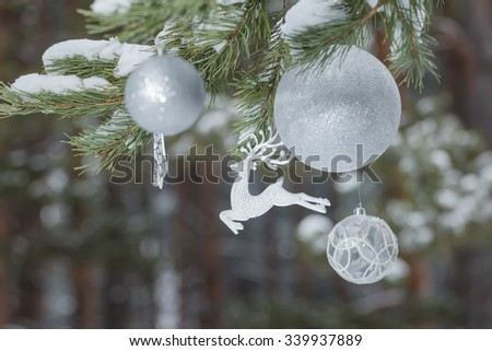 Winter pine tree branches with glitter reindeer ornament and Christmas baubles at snowy wood background - stock photo