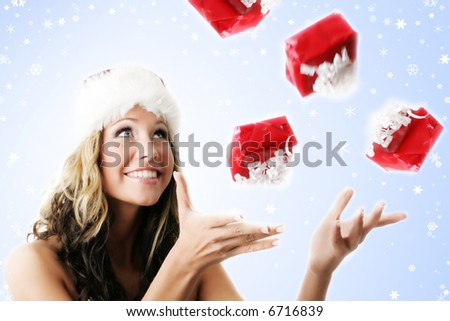 winter portrait of a beautiful young smiling woman with falling gifts - stock photo